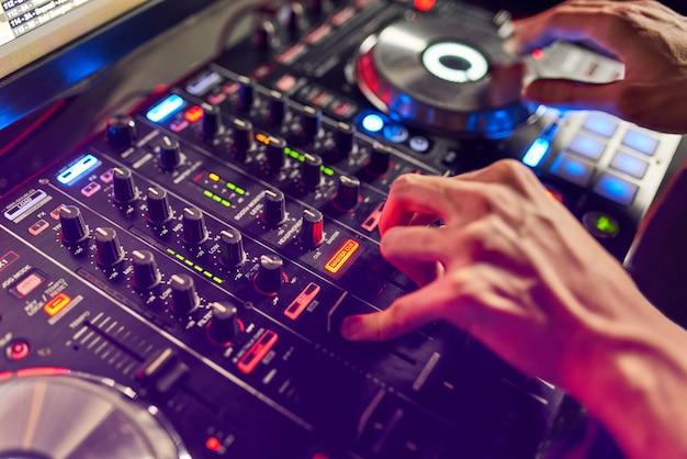 Dj mixe le morceau dans la boîte de nuit à la fête.