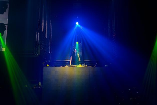Dj sur scène dans une discothèque disco mixant musique techno beat