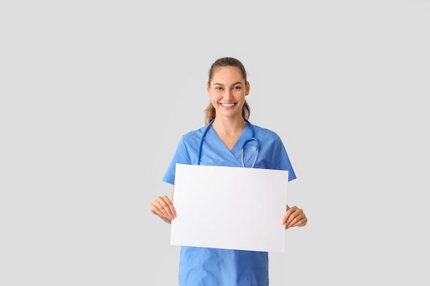 Docteur avec une affiche vierge sur fond clair