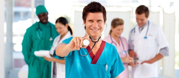 Docteur amical avec son équipe en arrière-plan