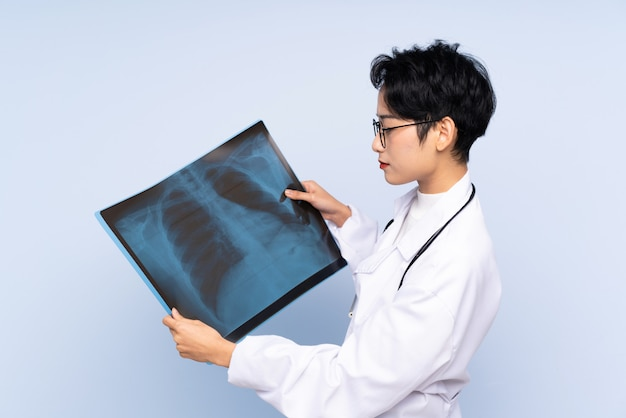 Docteur, asiatique, femme, tenue, os, balayage, isolé, bleu, mur