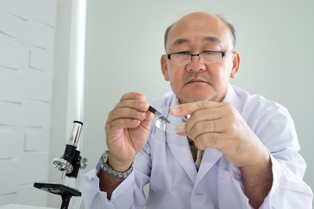 Docteur asiatique plus âgé ou sérieusement scientifique travaillant avec un microscope en laboratoire.