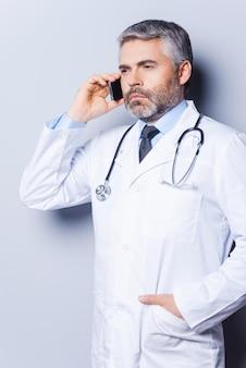 Docteur au téléphone. médecin de cheveux gris mûr et confiant parlant au téléphone portable et regardant loin en se tenant debout sur fond gris