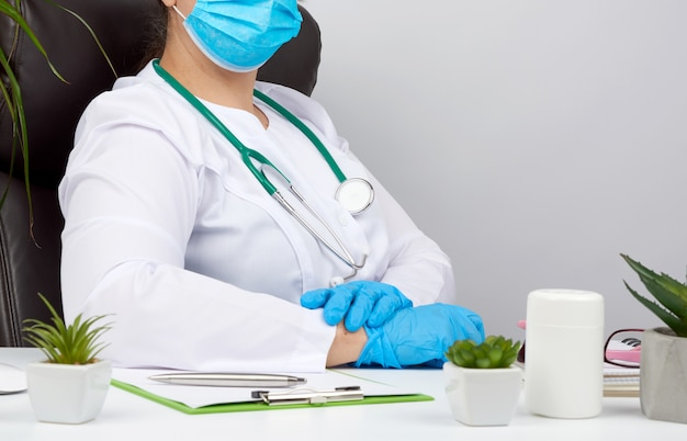 Docteur en blouse blanche et gants en latex bleu est assis à une table de travail blanche dans son bureau