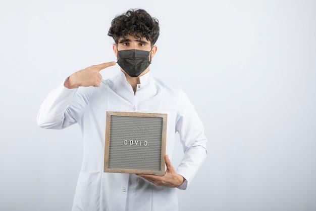 Docteur en blouse blanche avec stéthoscope pointant sur masque isolé sur blanc.