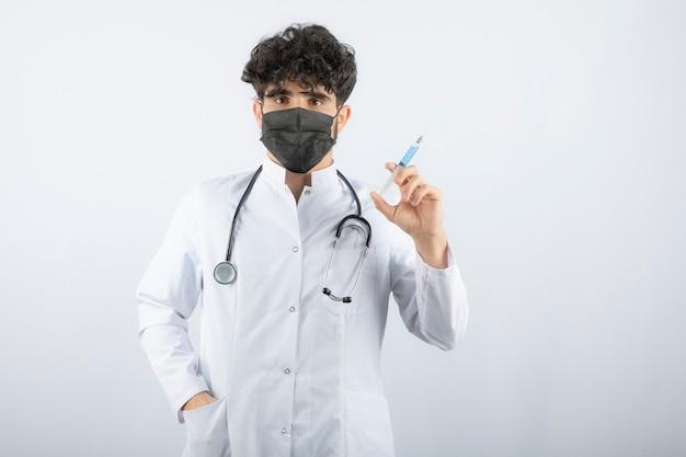 Docteur en blouse blanche avec stéthoscope tenant une seringue isolée sur blanc.
