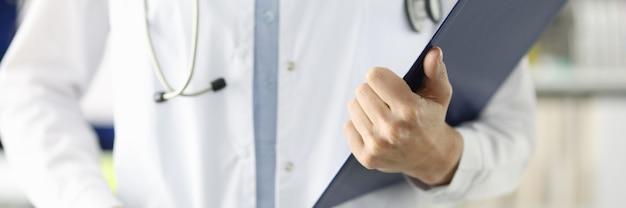Docteur en blouse blanche tenant un presse-papiers avec des documents en conseil médical professionnel de la clinique