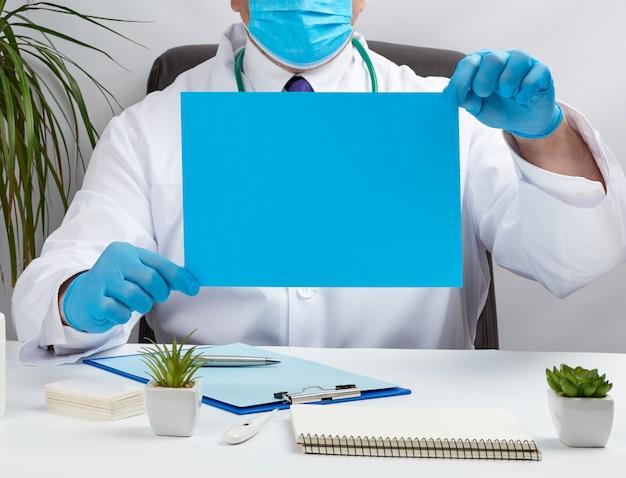 Docteur en blouse médicale blanche est assis à une table dans une chaise en cuir marron et tenant une feuille de papier bleu vide