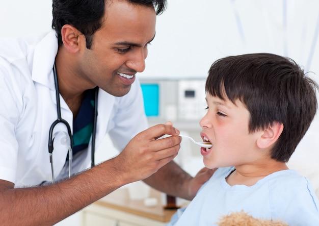 Docteur charismatique donnant des médicaments à un petit garçon