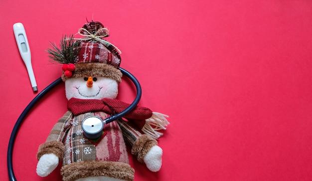 Docteur et concept de noël. bonhomme de neige malade et stéthoscope sur rouge