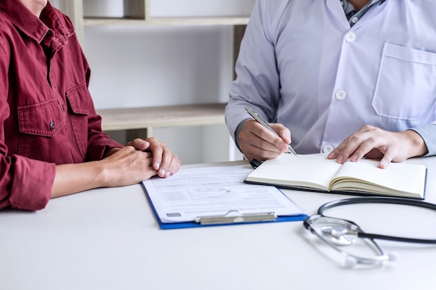 Docteur consultant un patient discutant et recommandant des méthodes de traitement, présentant les résultats dans un rapport
