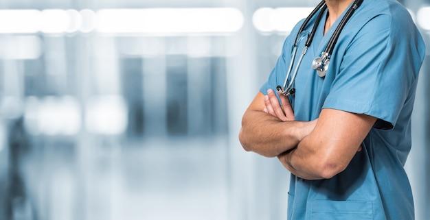 Docteur contre un arrière-plan flou bleu, photo impersonnelle, pas de visage.