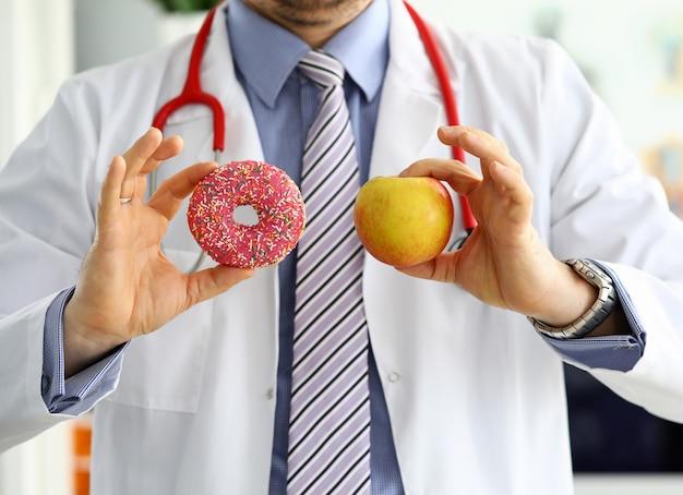 Docteur, dans, bureau, tenue dans main, rose, beignet, contre, pomme rouge, gros plan. produits qui ne peuvent pas être consommés dans certaines maladies