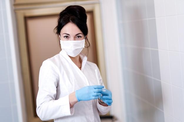 Docteur dans un masque médical. prendre un écouvillon de l'oropharynx. photographie conceptuelle - test pour le coronavirus. dans la main est un tube à essai avec un échantillon du patient.