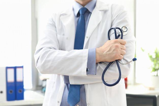 Docteur, debout, bureau, stéthoscope, main