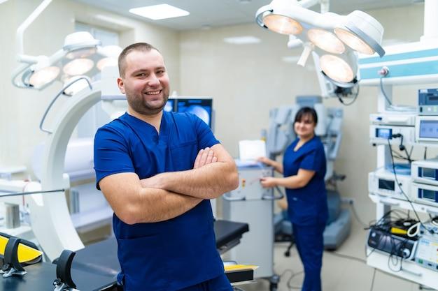 Docteur debout devant un équipement robotique spécial. médecin barbu souriant. femme infirmier en arrière-plan. concept d'hôpital et de chirurgie.