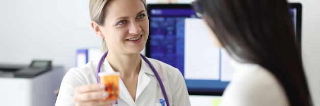 Docteur donnant la bouteille patiente de médecine dans la clinique