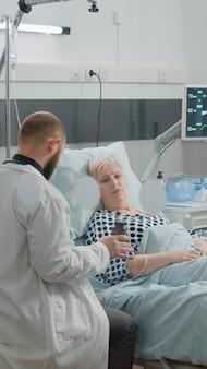 Docteur donnant une bouteille de pilules pour un vieux patient malade