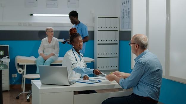 Docteur donnant le document de prescription avec le cachet au vieux patient