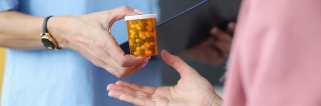 Docteur donnant le pot de pilules au patient agrandi