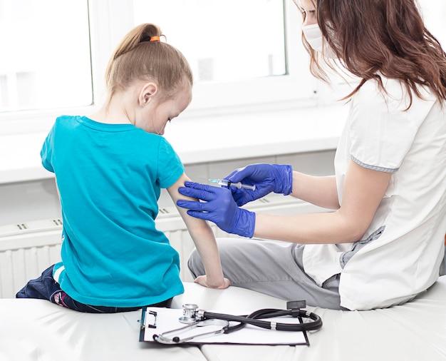 Le docteur donne une injection à une petite fille