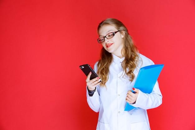 Docteur avec un dossier bleu et des lunettes vérifiant son téléphone.