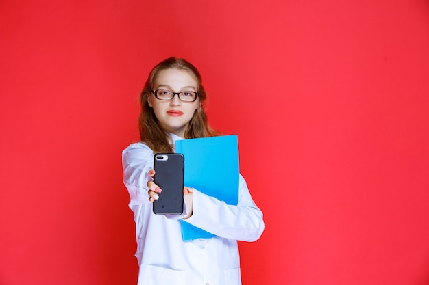 Docteur avec un dossier bleu montrant son téléphone.