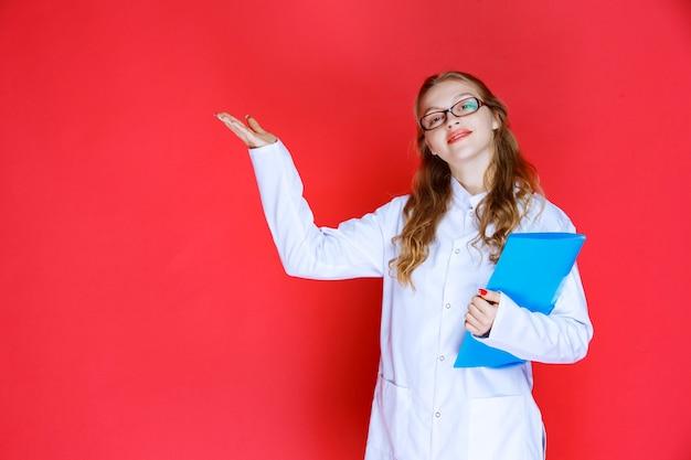 Docteur avec un dossier bleu pointant vers la gauche.