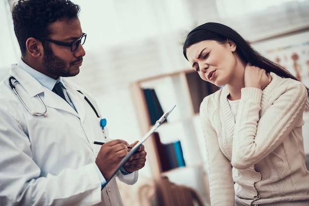 Le docteur écoute les symptômes de la femme. le cou de la femme me fait mal.