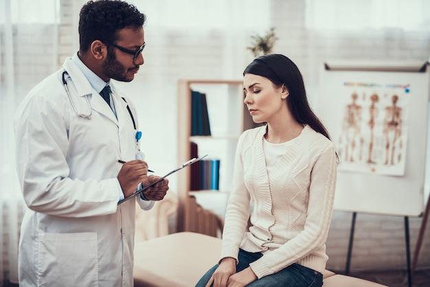 Le docteur écoute les symptômes de la femme.