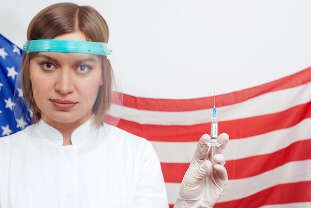 Docteur en écran facial de sécurité tenant la seringue avec le vaccin sur le drapeau des états-unis d'amérique
