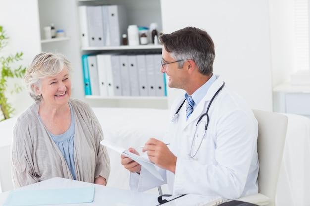 Docteur écrit des prescriptions pour une patiente âgée