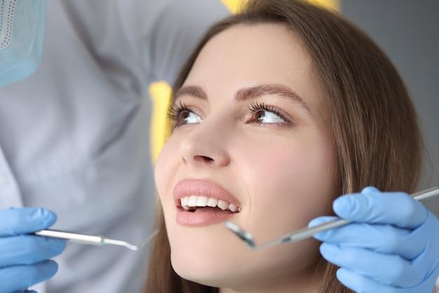 Le docteur effectue l'examen dentaire du patient de femme