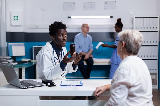 Docteur d'ethnie africaine tenant une bouteille de pilules pour un vieux patient