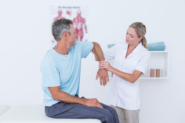 Docteur étire un bras d'homme