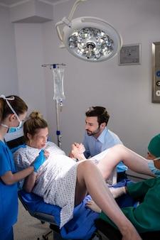 Docteur, examiner, femme enceinte, pendant, livraison, quoique, homme, tenant main, dans, salle opération