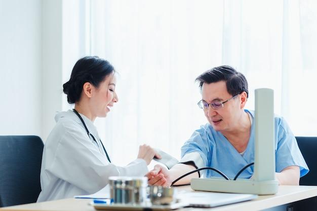 Docteur femmes mesurant le sang chez des hommes patients discutant avec un médecin au bureau de la clinique