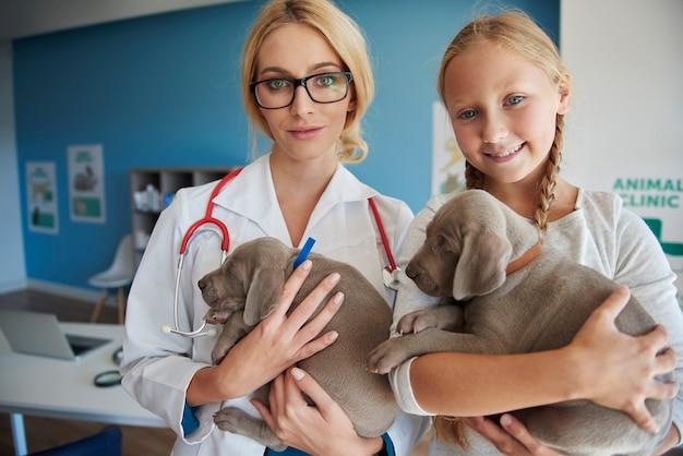 Docteur et fille tenant des chiots mignons