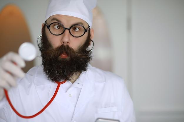 Docteur fou. un scientifique à la barbe folle mène des expériences dans un laboratoire scientifique. effectue des recherches à l'aide d'une seringue et d'un stéthoscope.