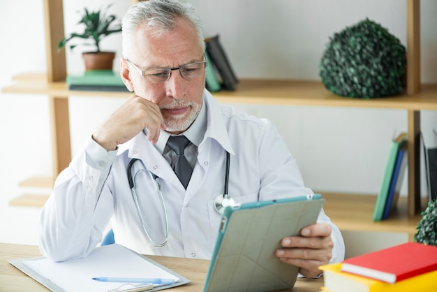 Docteur fronçant utilisant la tablette au bureau