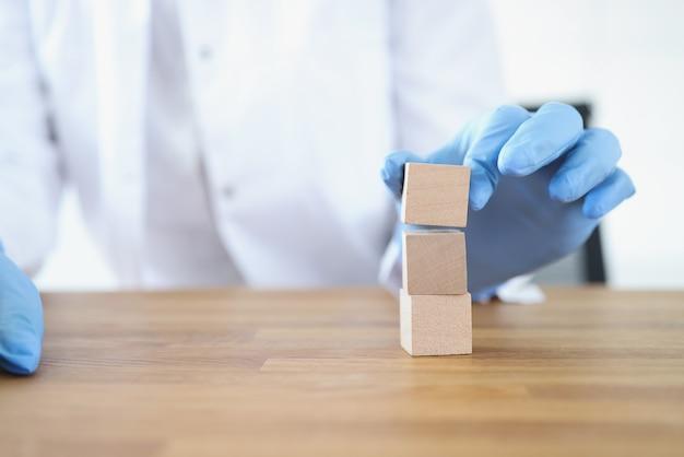 Un docteur ganté construit une tour de cubes en bois