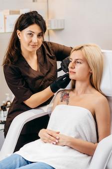 Docteur en gants donnant des injections de femme dans les lèvres