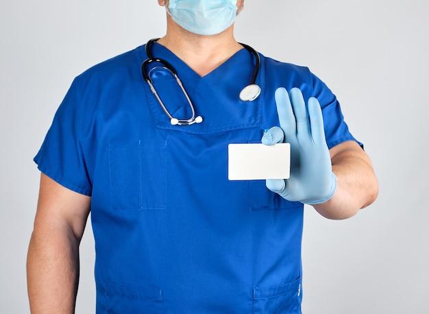 Docteur en gants en latex stériles et uniforme bleu est titulaire d'une carte de visite blanche vierge
