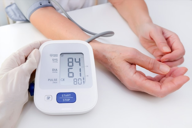 Docteur en gants mesure la pression artérielle d'une personne
