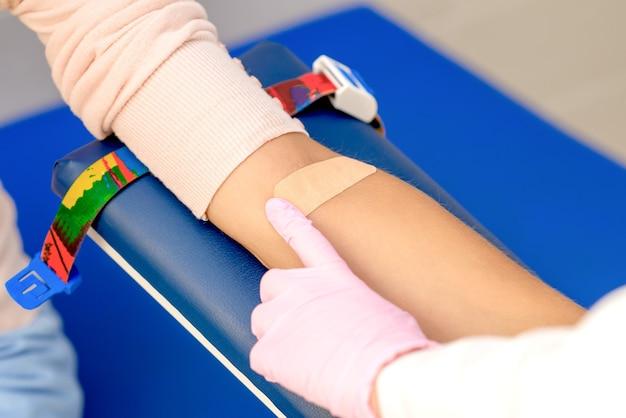 Un docteur en gants de protection en caoutchouc colle un pansement adhésif sur le bras après un prélèvement sanguin.