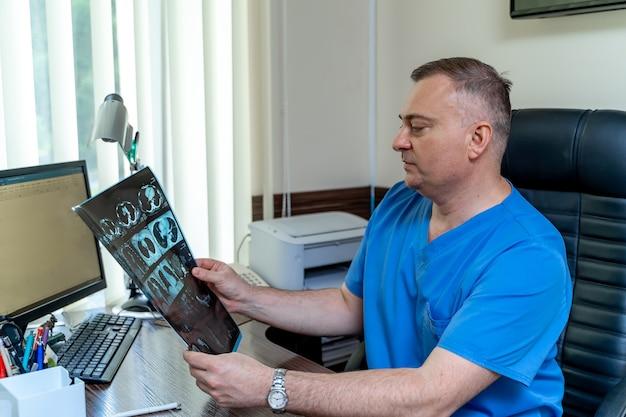 Docteur en gommage assis au bureau. radiographie dans les mains. résultats médicaux aux mains du médecin.
