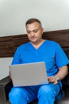 Docteur en gommages bleus se relaxant avec son ordinateur portable pendant la pause-café. mise au point sélective.
