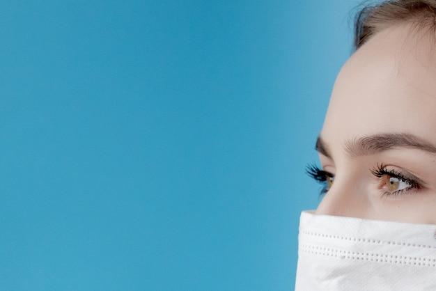 Docteur infirmière souriant derrière le masque de chirurgien. closeup portrait of young caucasian woman model sur fond bleu. femme, porter, masse, protéger, covid-19