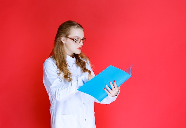Docteur avec des lunettes tenant un dossier flou.