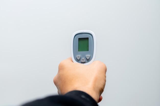 Docteur main tenant le pistolet de température sur une surface grise.